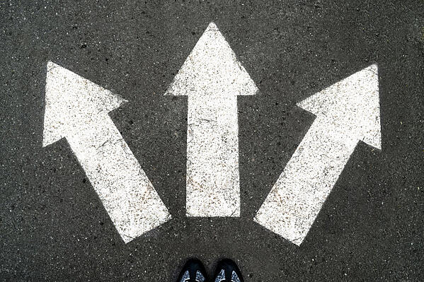 three-white-arrows-pointing-in-different-directions-on-gray-asphalt_72482-333